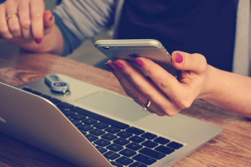 Pessoa com notebook e mexendo no celular