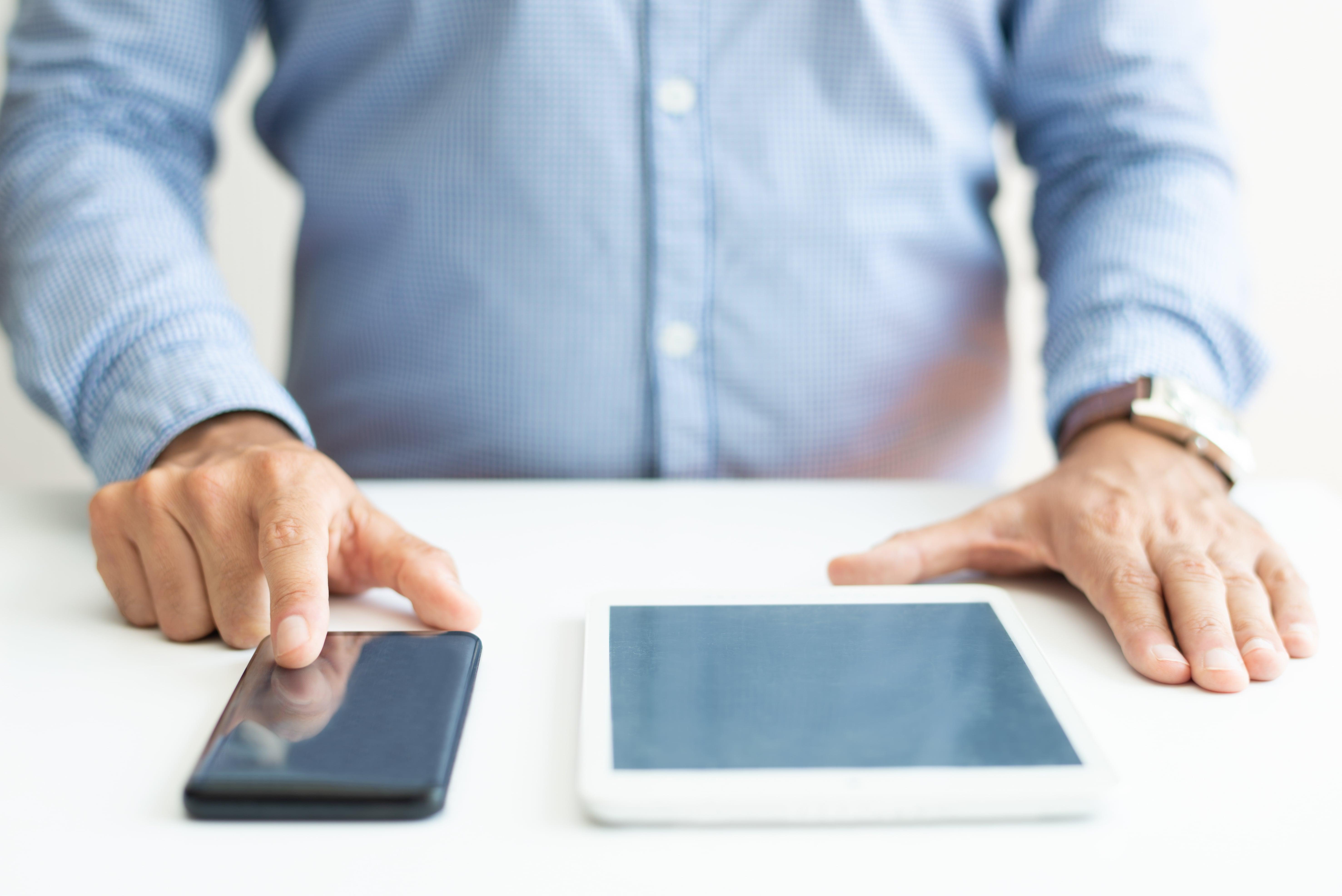 Pessoa com celular e tablet escolhendo software de gestão
